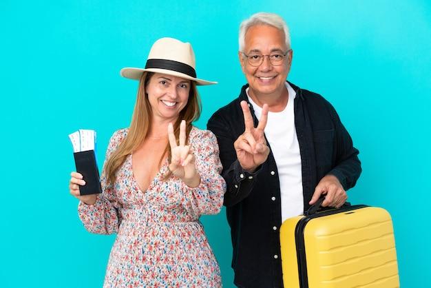 Casal de meia-idade vai viajar e segurando uma mala isolada em um fundo azul sorrindo e mostrando o sinal da vitória