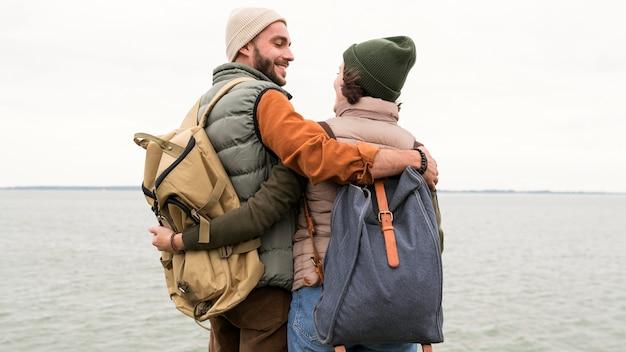 Casal de meio tiro se abraçando e se olhando perto do mar Foto Premium