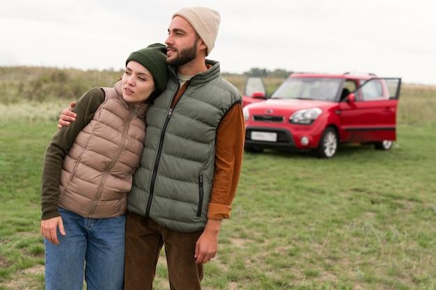 Casal de meio tiro se abraçando na frente do carro Foto Premium