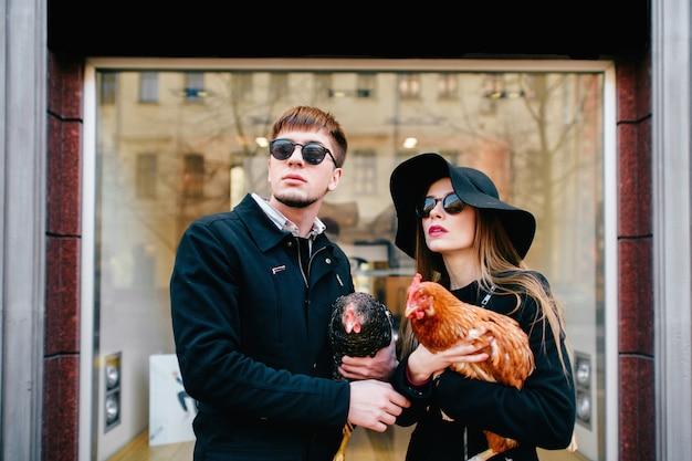 Casal de moda com frango nas mãos, posando em frente a vitrine de boutique