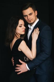 Casal de moda elegante abraços, um homem em uma jaqueta e uma menina grávida