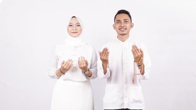 Casal de molem asiáticos rezando espaço em branco isolado