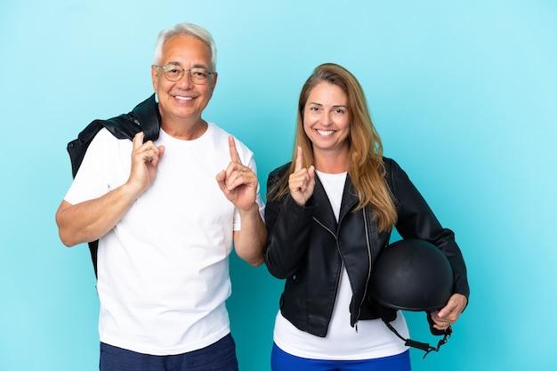 Casal de motociclistas de meia-idade com capacete de motociclista isolado em fundo azul, mostrando e levantando um dedo em sinal dos melhores