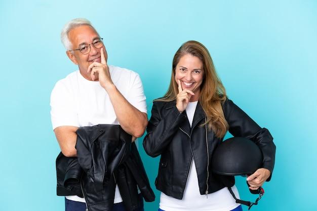 Casal de motociclistas de meia-idade com capacete de motociclista isolado em um fundo azul e sorrindo com uma expressão doce