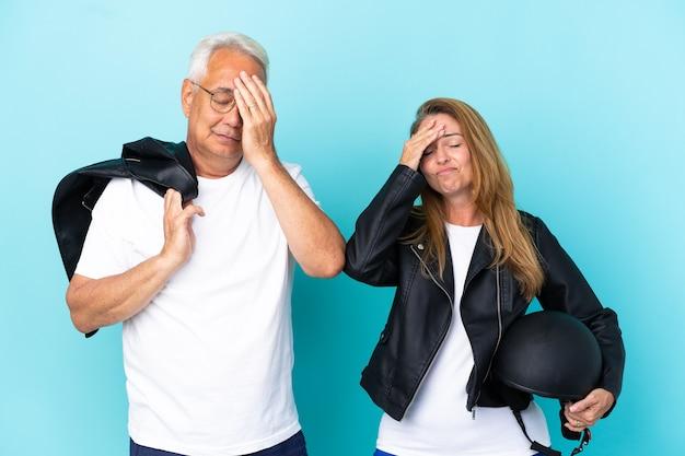 Casal de motociclistas de meia-idade com um capacete de motociclista isolado em um fundo azul com expressão facial de surpresa e choque