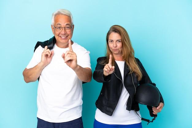 Casal de motociclistas de meia-idade com um capacete de motociclista isolado em um fundo azul, mostrando e levantando um dedo