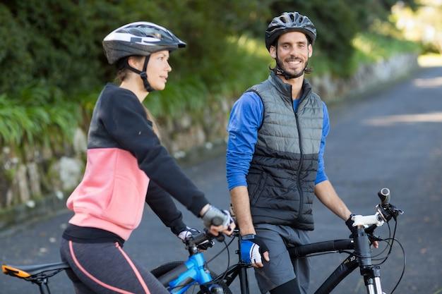 Casal de motoqueiros com bicicleta de montanha na estrada