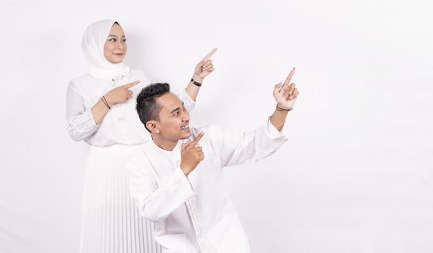 Casal de muçulmanos asiáticos apontando para um espaço em branco isolado de tela em branco