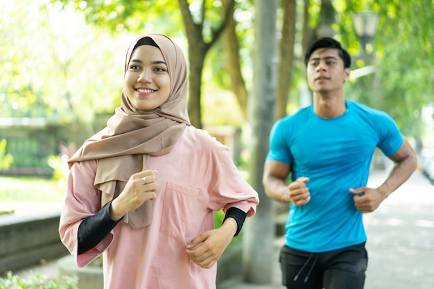Casal de muçulmanos fazendo jogging juntos durante exercícios ao ar livre no parque
