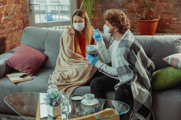 Casal de mulher e homem com máscaras protetoras e luvas isoladas em casa com coronavírus