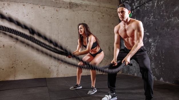 Casal de mulher e homem treinando juntos a fazer exercícios de luta contra a corda