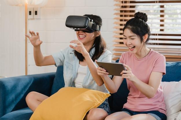 Casal de mulheres asiáticas lgbtq lésbicas jovens usando tablet em casa