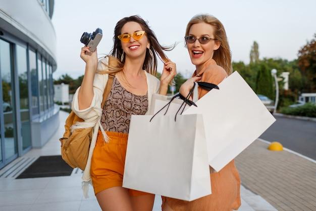 Casal de mulheres elegantes depois de sair da viagem e fazer compras posando ao ar livre perto do aeroporto