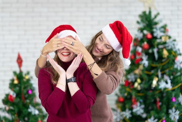 Casal de mulheres felizes usando fantasia de papai noel, sorrindo e rindo com as mãos no rosto cobrindo os olhos de surpresa