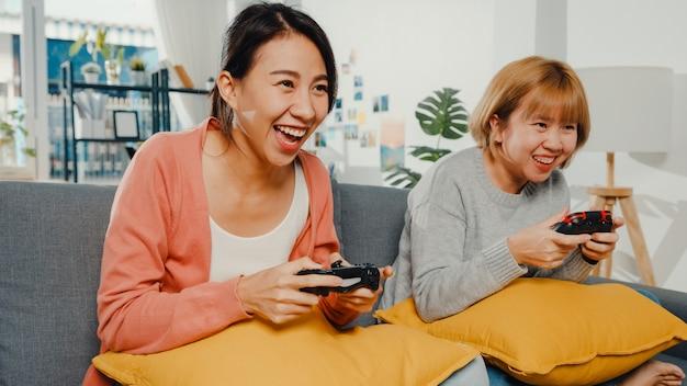 Casal de mulheres joga videogame em casa.
