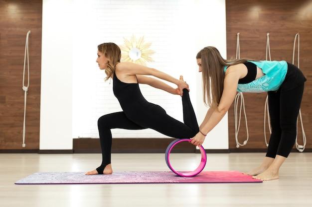 Casal de mulheres jovens em uma yoga sportswear exercícios com uma roda de ioga no ginásio