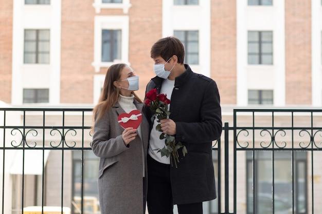 Casal de namorados com presente na máscara facial.