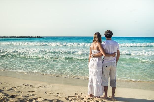 Casal de namorados de costas, olhando para o mar do caribe