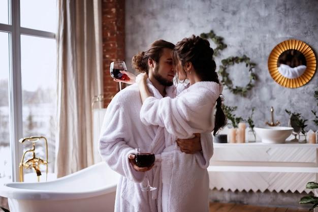 Casal de namorados em roupões de banho com taças de vinho no banheiro. relaxar