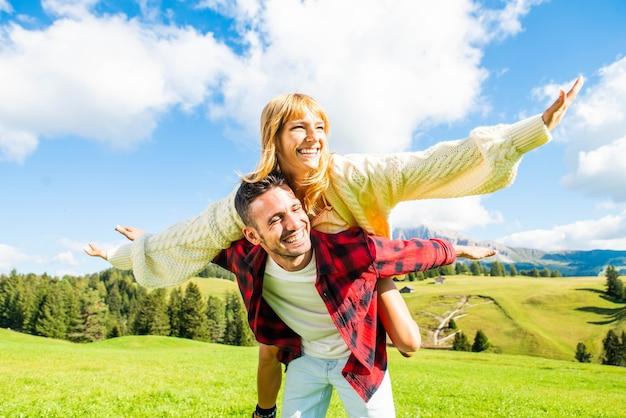Casal de namorados se divertindo pegando carona no campo da primavera