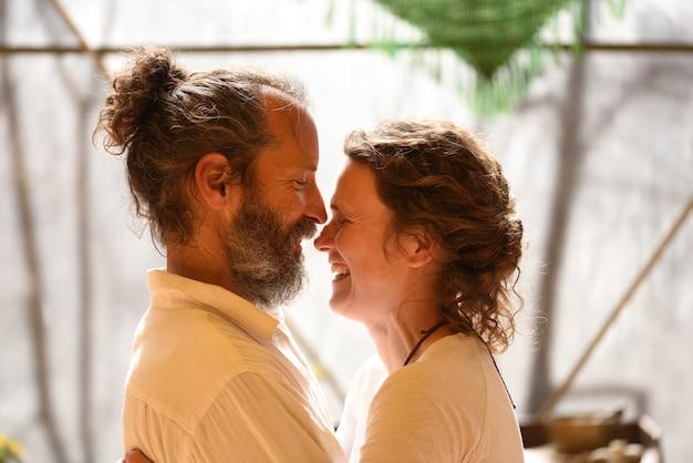 Casal de namorados se encarando de perfil e rindo