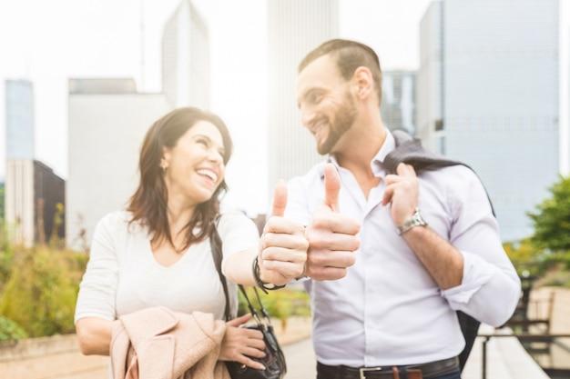 Casal de negócio bem sucedido mostrando os polegares