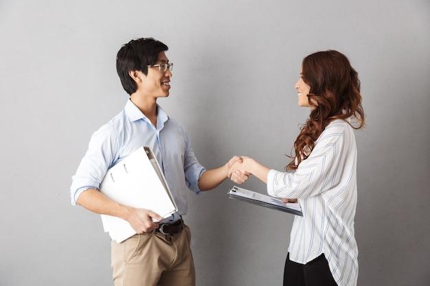Casal de negócios asiáticos feliz trabalhando junto com documentos