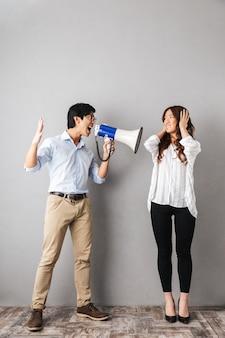 Casal de negócios asiáticos zangados parado isolado, homem segurando um alto-falante e gritando