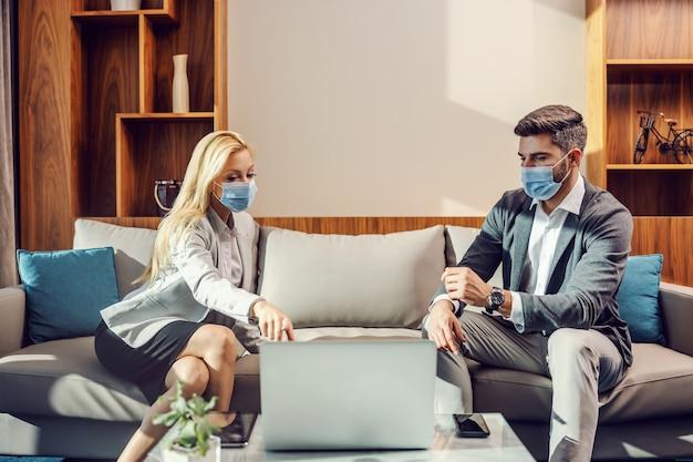 Casal de negócios com máscaras, sentado no escritório e tendo uma reunião