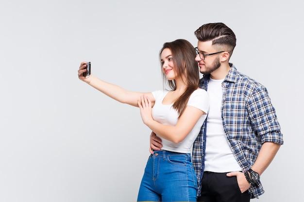 Casal de negócios em pé, abraçando e segurando um telefone celular