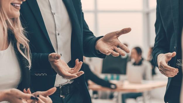Casal de negócios falando sobre algo em pé no escritório