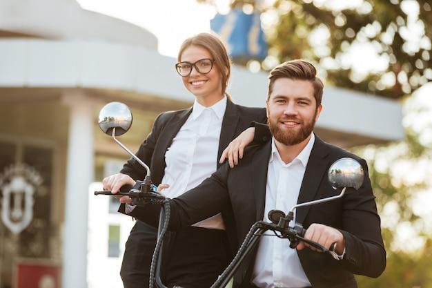Casal de negócios feliz posando com moto moderna ao ar livre