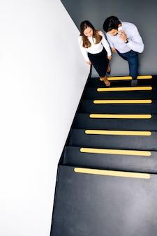 Casal de negócios jovem nas escadas no escritório