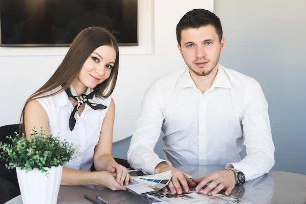 Casal de negócios orgulhosos olhando para a câmera, sentado no escritório. casal de negócios orgulhosos olhando para a câmera