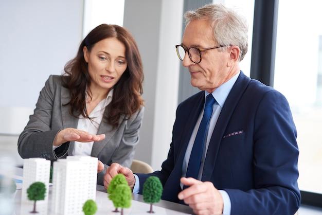 Casal de negócios sobre modelo arquitetônico