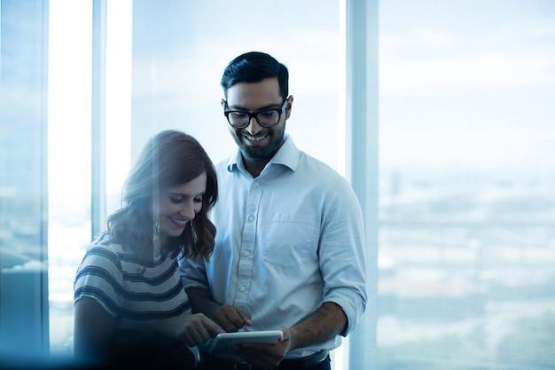 Casal de negócios sorridente usando tablet digital contra janela de vidro