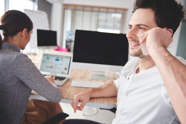 Casal de negócios usando tecnologia sem fio no trabalho