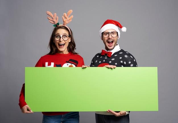 Casal de nerds segurando banner de natal em tela verde com espaço de cópia