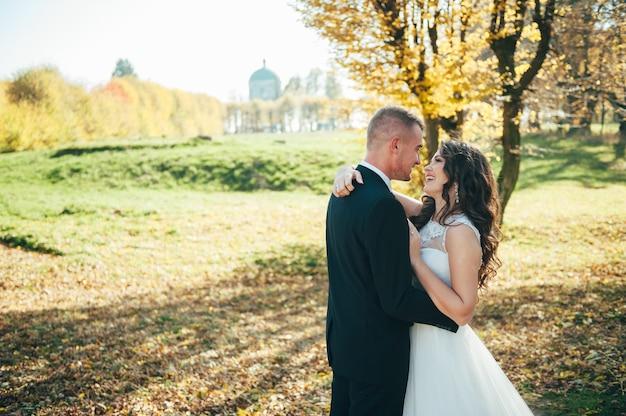 Casal de noivas feliz caminhando no parque de outono