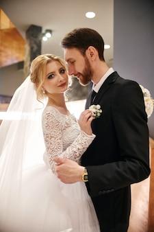 Casal de noivos abraçando e beijando, o primeiro dia de vida juntos. noiva e noivo após a cerimônia de casamento, lindo casal se ama e abraçando