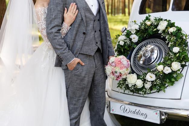 Casal de noivos abraçando perto de carro de casamento com buquê e a palavra