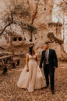 Casal de noivos apaixonados, homem e mulher caminhando na floresta de outono