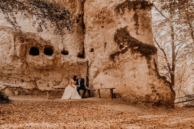 Casal de noivos apaixonados, homem e mulher, sentados em um banco sob o mosteiro de rocha bakota na floresta de outono