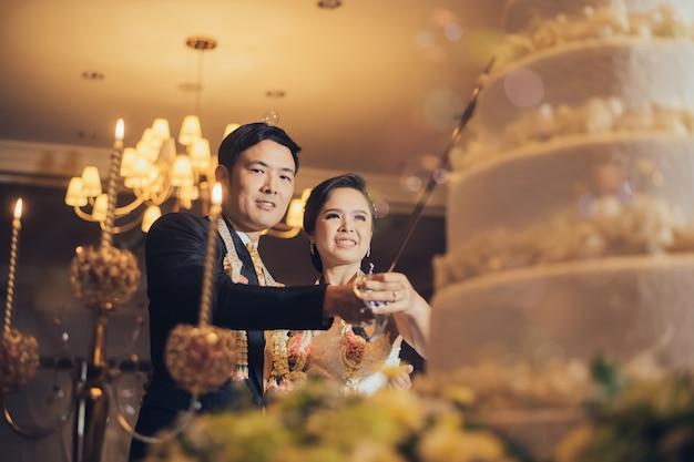Casal de noivos asiáticos na frente do bolo