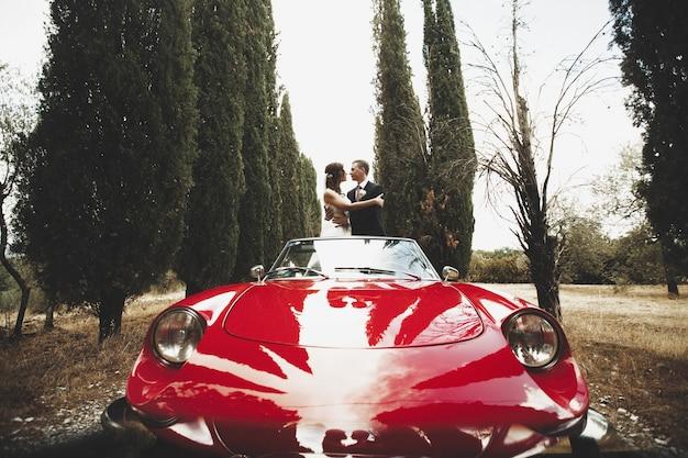 Casal de noivos beijando em um cabrio vermelho que fica entre árvores altas