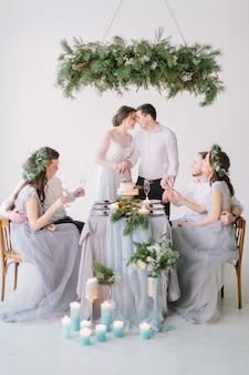Casal de noivos beijando na mesa de casamento decorada com suas madrinhas e padrinhos