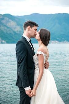Casal de noivos beijando no fundo de um lago e montanhas