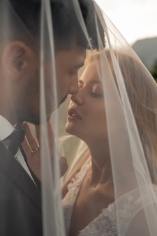 Casal de noivos beijos sob o véu.