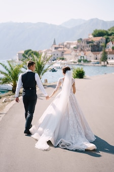 Casal de noivos caminha ao longo da barragem perto do mar, tendo como pano de fundo palmeiras, montanhas e a cidade velha