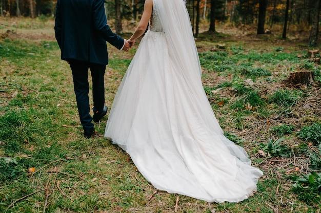 Casal de noivos caminhando de volta na natureza. noiva em um vestido e o noivo vão em uma floresta verde.